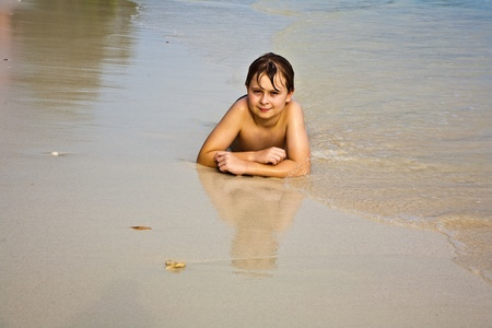 young boy is lying at the beach and enjoying the warmness of the water and looking self confident and happy Stock Photo - 9583336