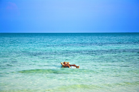 matress: man lying on an air matress in the sea is enjoing the sun and relaxing Stock Photo