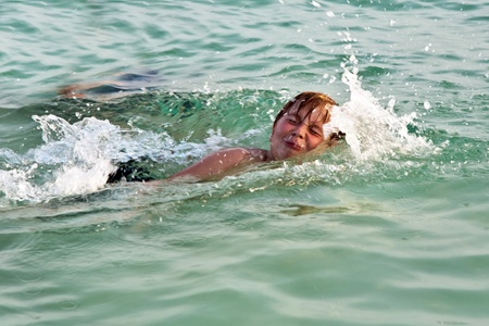 young boy enjoys swimming in the clear warm salt water in the sea photo