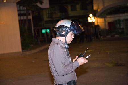 calm down: BANGKOK, Thailandia - 6 maggio: Polizia cerca di calmare demonstrants - fornitori di Patpong Night Market che manifestare contro confiscando loro falso marchio plagiates, poliziotto, utilizzando il suo cellulare, Padpong mercato, 6 maggio 2009 a Bangkok, Thailandia Editoriali