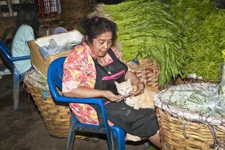 BANGKOK, THAILAND - May 12: women are selling fresh flowers and hugging with a cat at the morning market Pak Khlong Thalat in Chinatown,  May 12, 2009 in Bangkok, Thailand