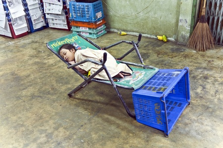 klong: BANGKOK, THAILAND - MAY 12: unidentified young girl sleeps in the shop of the flower market Pak Klong Thalat early morning on May 12,2009 Editorial