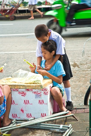 BANGKOK, THAILAND - MAY 12: unidentified children are working binding flowers before school starts on flower market Pak Klong Thalat early morning on May 12,2009