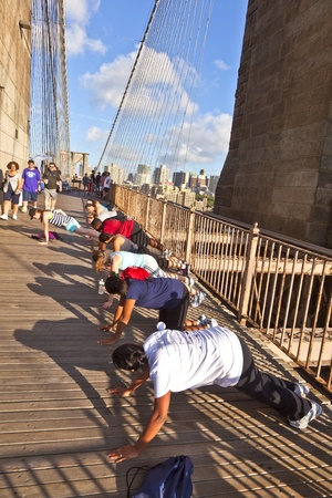 NEW York, USA - July 7: people are doing push-up exercises at the Brooklyn bridge in the late afternoon on July 7,2010 Stock Photo - 9522298