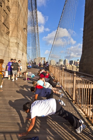 NEW York, USA - July 7: people are doing push-up exercises at the Brooklyn bridge in the late afternoon on July 7,2010