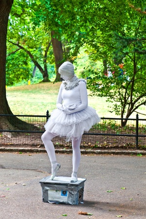 NEW YORK - JULY 11: Woman dressed as a ballet dancer in white shows pantomines to collect money for Amnesty International in the collecting boy at the Central Park on July 11,2010 in New York, USA.