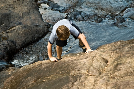 young boy climbing up a rock photo