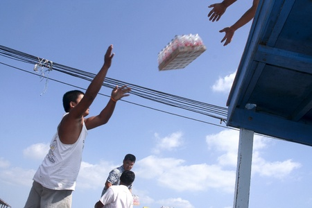 koh samet: KOH SAMET, THAILAND - DECEMBER 04:  Man is loading the ferry by throwing goods for tourist resorts  to his partner at the roof  on December 04, 2006 in Koh Samet, Thailand. Editorial