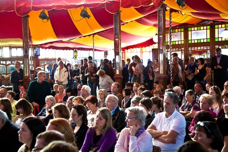 eading: FRANKFURT, GERMANY - OCTOBER 10: public day for Frankfurt Book fair, spectators are listening the authors in the reading tent on October 10, 2010 in Frankfurt, Germany.