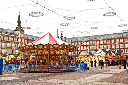 MADRID, SPAIN - DECEMBER 20: People have fun in Christmas time on the carrousell for children in the evening at the plaza de Mayor in Madrid on December 20, 2010 in Spain.