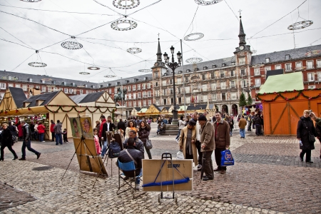 MADRID, SPAIN - DECEMBER 20: People have fun in Christmas time and have a portrait by an artist in the evening at the plaza de Mayor in Madrid on December 20, 2010 in Spain. Stock Photo - 9541730