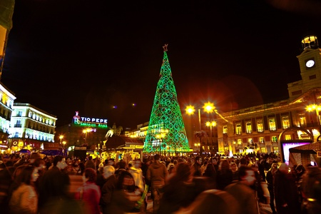 MADRID, SPAIN - DECEMBER 22: People have fun in Christmas time passing the famous illuminated christmas tree at puerta del sol on December 22, 2010 in Madrid, Spain. Stock Photo - 9541634