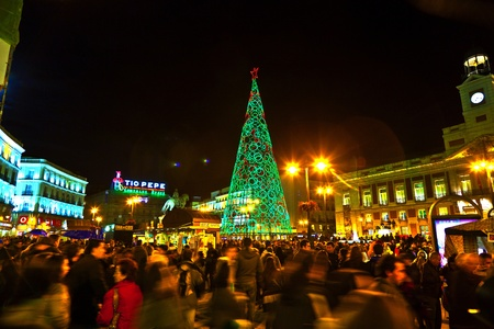 sol: MADRID, SPAIN - DECEMBER 22: People have fun in Christmas time passing the famous illuminated christmas tree at puerta del sol on December 22, 2010 in Madrid, Spain.