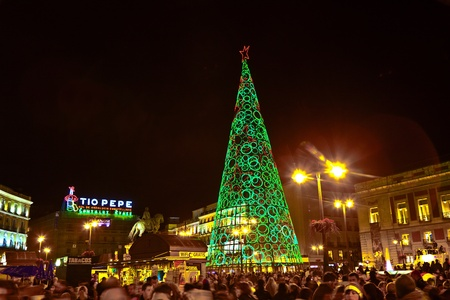 MADRID, SPAIN - DECEMBER 22: People have fun in Christmas time passing the famous illuminated christmas tree at puerta del sol on December 22, 2010 in Madrid, Spain.