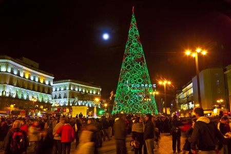 plaza: MADRID, SPAIN - DECEMBER 22: People have fun in Christmas time passing the famous illuminated christmas tree at puerta del sol on December 22, 2010 in Madrid, Spain.