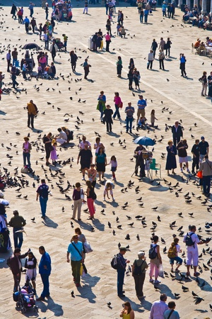VENICE, ITALY - 04 JULY: Tourists on San Marco square feed large flock of pigeons on July 04, 2007. San Marco square is the largest and most famous square in Venice.