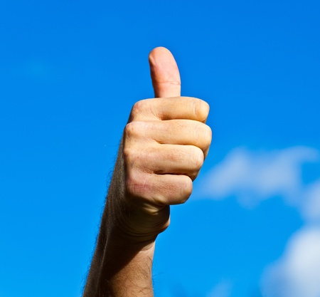 Thumbs up hand sign with sky photo
