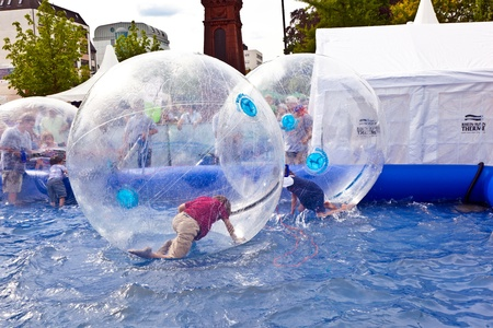 OBERURSEL, GERMANY - June 12: girls and boys have fun in a huge zorbing ball  on June 12, 2011 in Oberursel, Germany. Hessentag is a big festival to present a city in the county of Hesse in Germany.