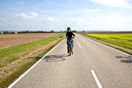 young boy on his mountain bike is on a bicycle tour along beautiful countryside photo