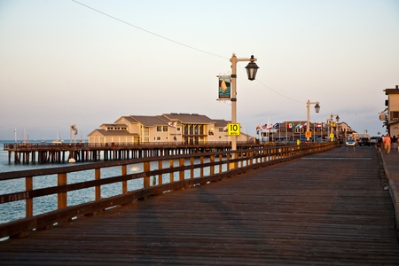 SANTA BARBARA, USA - JULY 28: people visiting scenic pier in SAnta barbara in sunset  on JULY 28, 2008 in Santa Barbara, USA. First built in 1872, the wharf ranked as the longest deep-water pier. photo