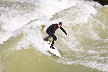 MUENCHEN, GERMANY - APRIL 07: People surfing on the Isar for season opening contest on April 07,2009 Munich. Surfing on the Isar and watching is a famous touristic attraction. photo