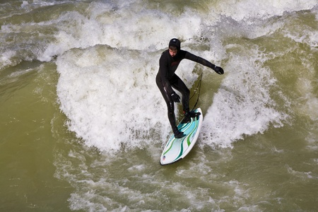 MUENCHEN, GERMANY - APRIL 07: People surfing on the Isar for season opening contest on April 07,2009 Munich. Surfing on the Isar and watching is a famous touristic attraction.