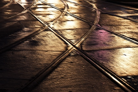 reflecting: wet trolley railes in the light and streets are reflecting light 스톡 사진