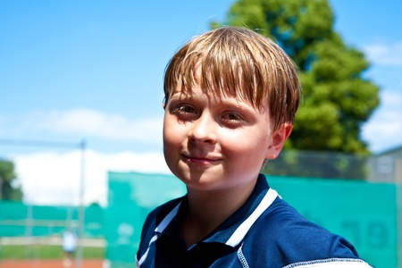 child looks happy and satisfied after the tennis match photo