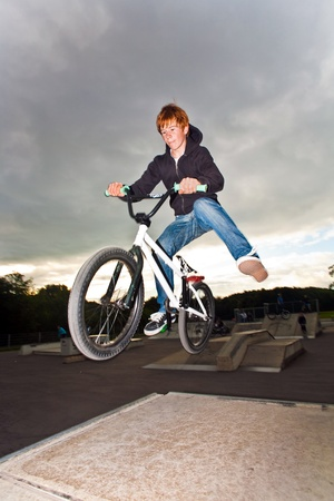 bmx: joung red haired boy is jumping with his BMX Bike at the skate park with fun