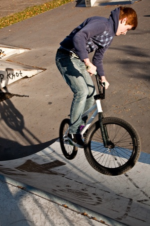 joung red haired boy is jumping with his BMX Bike at the skate park with fun photo