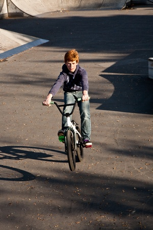 bmx bike: joung red haired boy is jumping with his BMX Bike at the skate park with fun