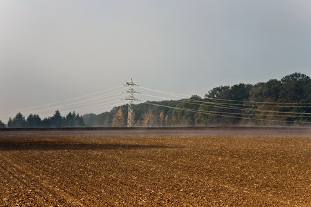 a pylon will be setted up in foggy weather in beautiful\ landscape with acres in fog