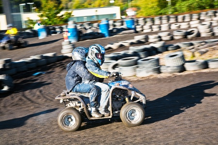 child loves to race with a quad at the muddy quad track photo