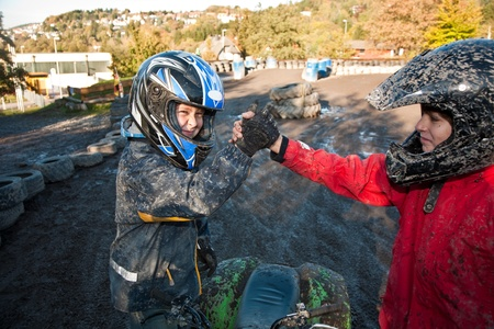 changing course: child loves to race with a quad bike at the muddy quad track Stock Photo