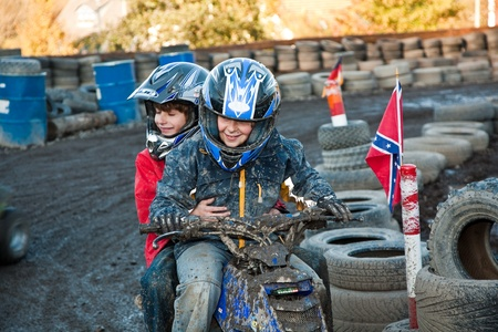 child loves to race with a quad bike at the muddy quad track photo