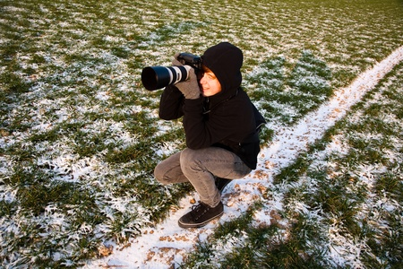 young boys are taking pictures of acres with snow in winter in beautiful light and structure photo