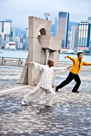 HONG KONG - JANUARY 8: Tai Chi Public Exercising in early morning at January 08, 2010 in Hongkong.  The old teacher teaches younger people to learn Tai Chi in the harbor area free of charge to keep tradition alive.