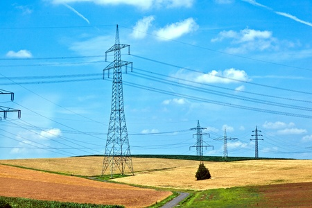 electrical power line with wind generator in rural landscape photo