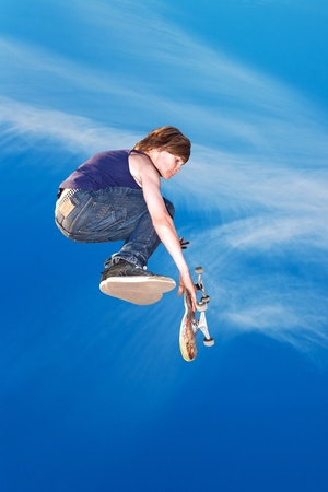 boy jumping with his skate board in the sky photo