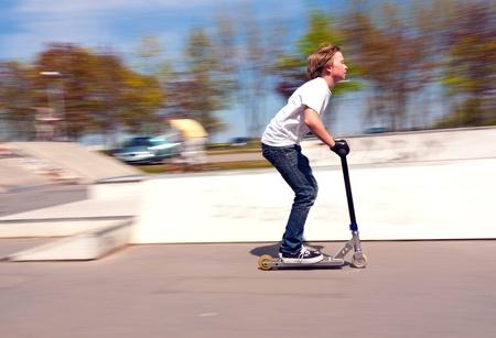 vespa: ni�o montado con velocidad en su scooter Foto de archivo