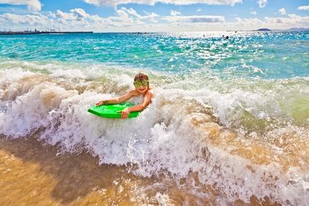 playa blanca: boy has fun with the surfboard at the beach Stock Photo