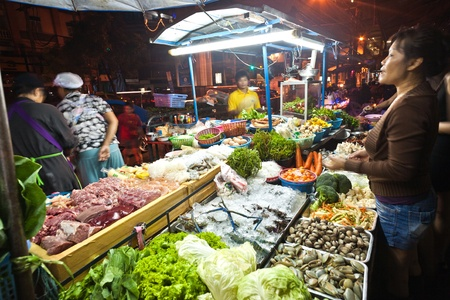 BANGKOK - DEC 21: fresh fish and vegetables  offered at the night market in Sukhumvit road at a foodstand  on December 21, 2009 in Bangkok, Thailand.  Most daily products in Bangkok are still sold on local asian markets. Stock Photo - 10105001