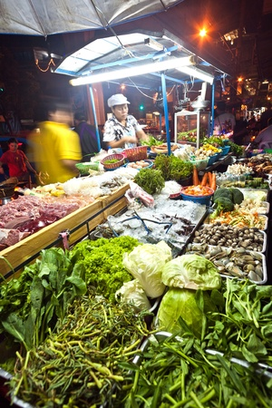 BANGKOK - DEC 21: fresh fish and vegetables  offered at the night market in Sukhumvit road at a foodstand  on December 21, 2009 in Bangkok, Thailand.  Most daily products in Bangkok are still sold on local asian markets.