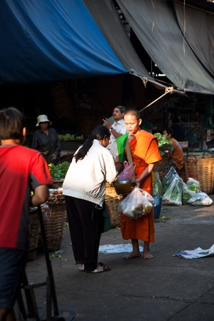 BANGKOK, THAILAND - December 23: people donate food to the monk on December 23,2009 in Bangkok, Thailand. Mendicant Monks life by donations from the people and giving to them means good luck for the day.