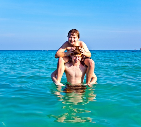 brothers are enjoying the clear warm water at the beautiful beach and playing pickaback Stock Photo - 10161631