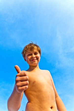 happy smiling young boy with background blue sky gives fingersign all-right, thumbs-up photo