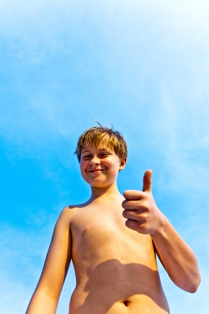 happy smiling young boy with background blue sky gives fingersign all-right, thumbs-up Stock Photo - 10161963
