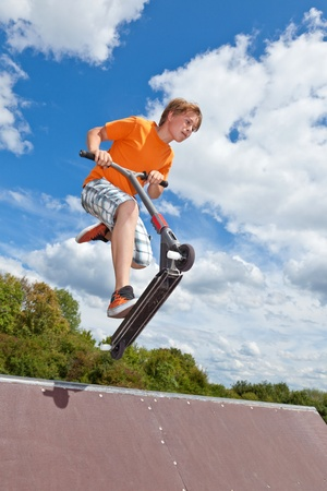 boy jumping with his scooter over a ramp in the skate park photo
