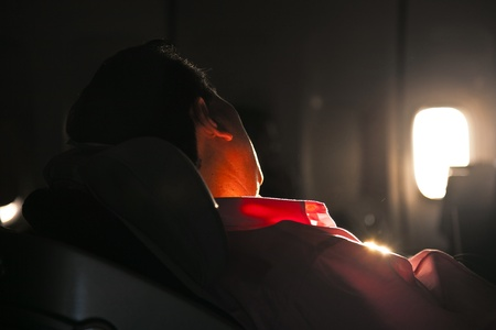 passenger vehicle: man sleeping in the seat of an aircraft in sunrise