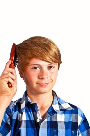 young boy brushing his hair photo